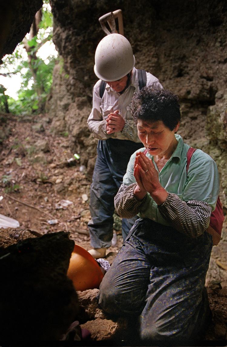 大岩の下から兵士の遺骨が掘り出された。その現場で祈る井上徳男さんと富美子さんご夫妻。沖縄で戦死した兄の遺骨を探しに北海道から15年間通って来られた、沖縄本島南部で