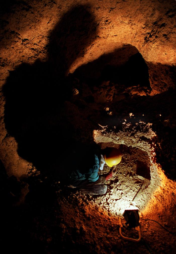 元地盤まで掘り下げる国吉勇さん。深い穴に長い影が伸びる