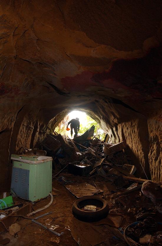 ゴミが捨てられている海軍の手掘りの壕。中の壁面は火炎放射器で焼かれて真っ赤に染まっている