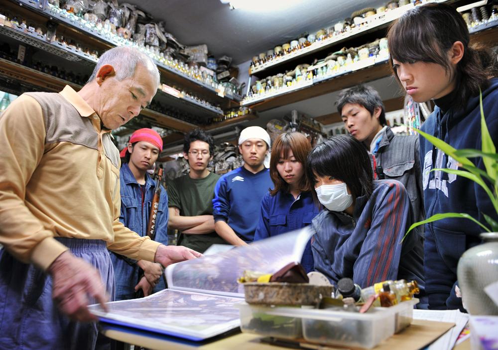 戦争資料館で国吉さん(左端)から説明を受けるボランティアの学生たち