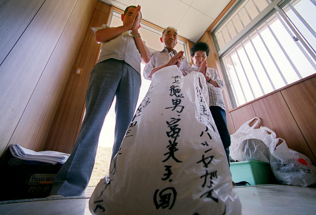 国吉さん(左端)と一緒に納骨する井上夫妻、本島南部の沖縄戦没者墓苑で