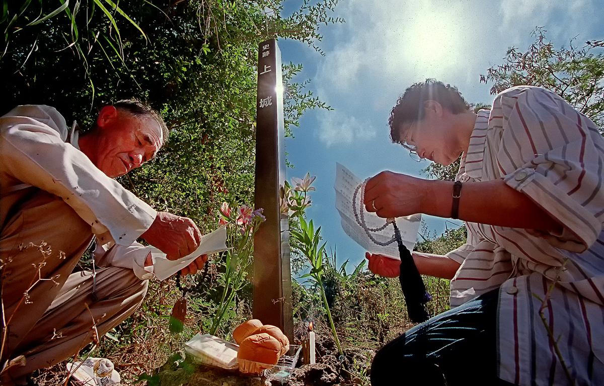 兄の戦死公報に記されていた地名の標識の下で、慰霊の祈りを捧げる徳男さんと富美子さん。この標識を墓標代わりにしている、沖縄本島南部の旧具志頭村で