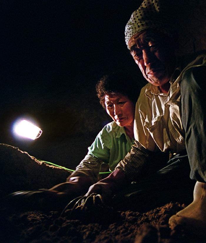 壕内の地面をかっちゃぎで掘る井上夫妻、旧具志頭村で