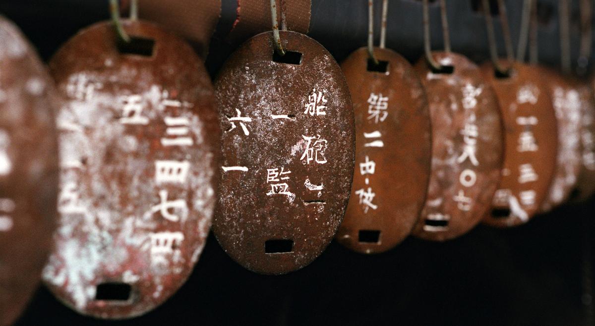 国吉戦争資料館に展示される鉄製の認識票。錆びてボロボロだ