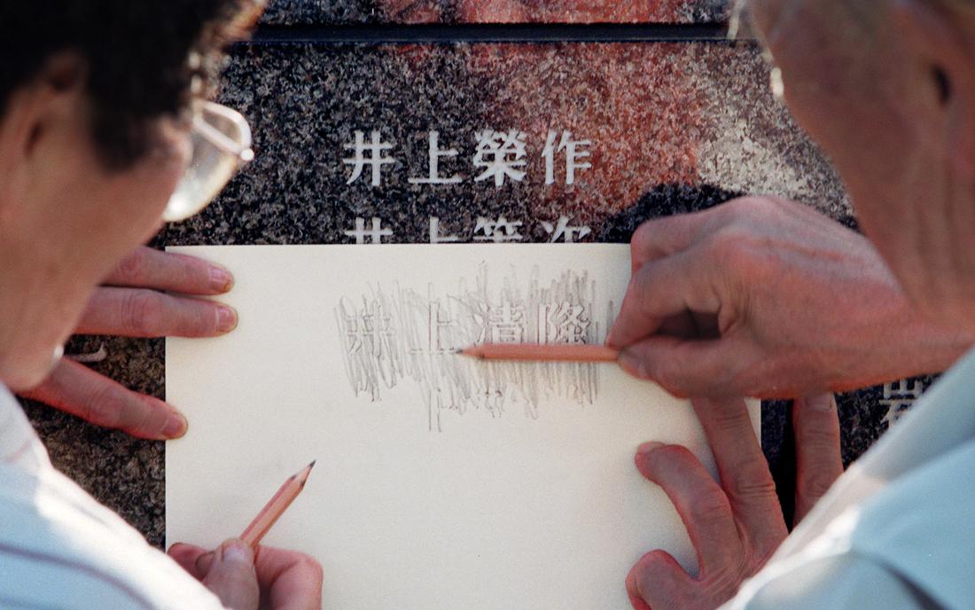 戦死した兄の名を平和の礎から紙に複写する井上夫妻、本島南部の摩文仁の丘で