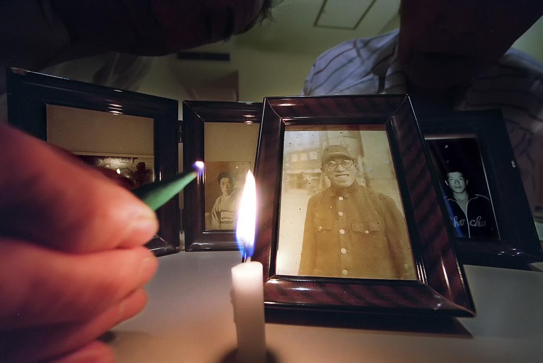 兄清隆さんの遺影にロウソクを灯す夫妻。宿泊先のホテルでも、毎朝祈りを捧げていた