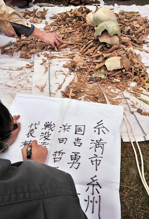 お骨を遺骨収集袋に詰める作業。布袋に発掘場所と収集に関わった人の名前を書き込む