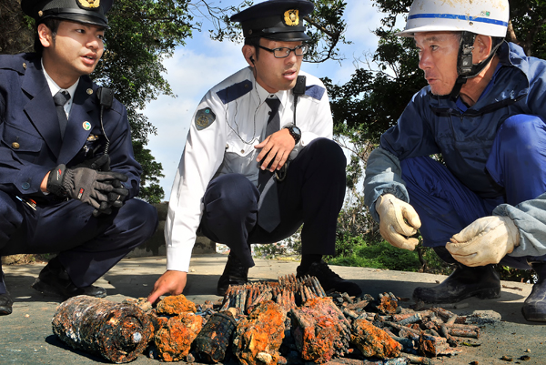 通報を受けて駆けつけた警察官。銃弾の数の多さに目を丸くしながら、遺骨収集家の国吉勇さんの話を聞いていた