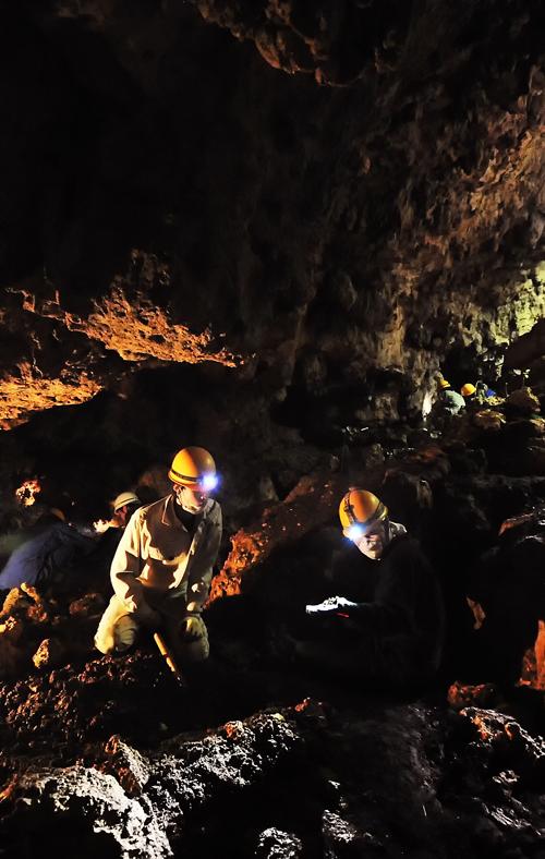 暗い壕内で遺骨収集活動をする学生たち、糸満市国吉で