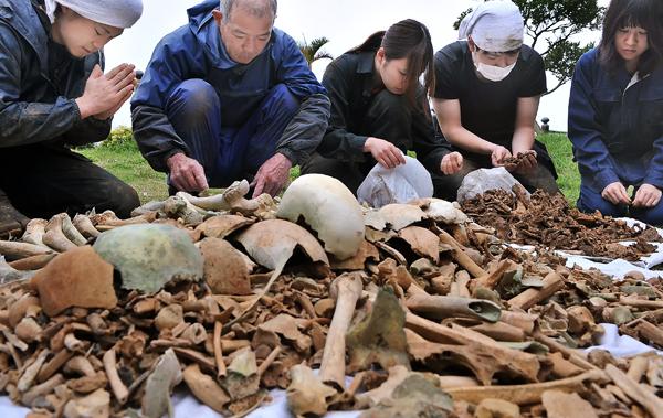 国吉さん(左から二人目)と一緒に遺骨の選別をするJYMA(日本青年遺骨収集団)の学生たち。遺骨に触れる前に、そっと手を合わせ冥福を祈っていた。糸満市大度で