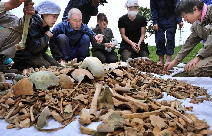 国吉勇さん(左から3人目から、遺骨の部位の説明などを受ける学生たち