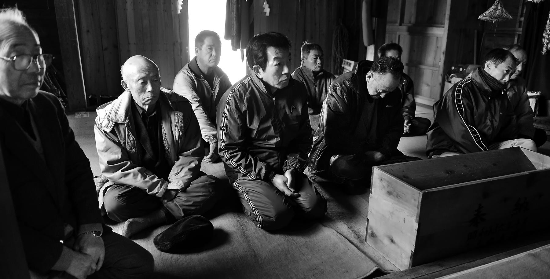 氷点下の朝、板の間の床に座って始まるのを待つ地区の方々
