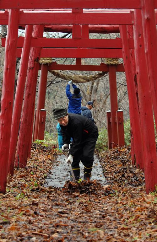 稲荷神社らしい真っ赤な鳥居が並ぶ。この一の鳥居にしめ縄を飾る