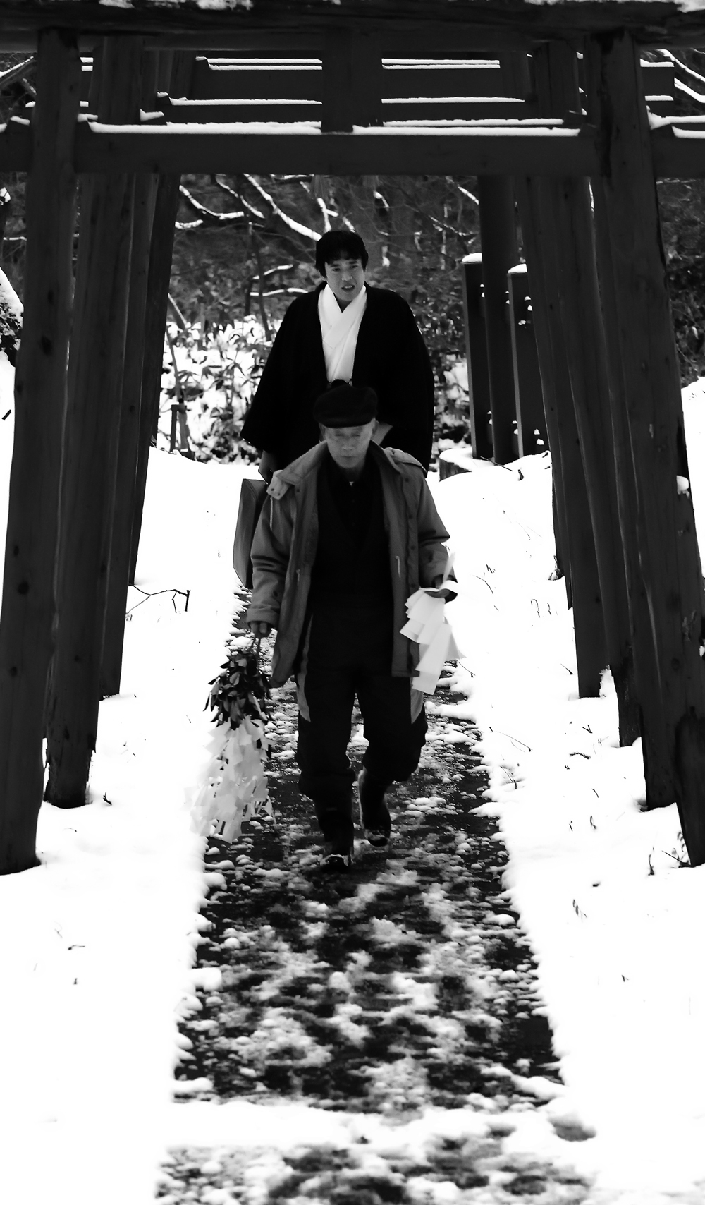 前夜、降り積もった雪が残る山道を登ってくる神主さんら