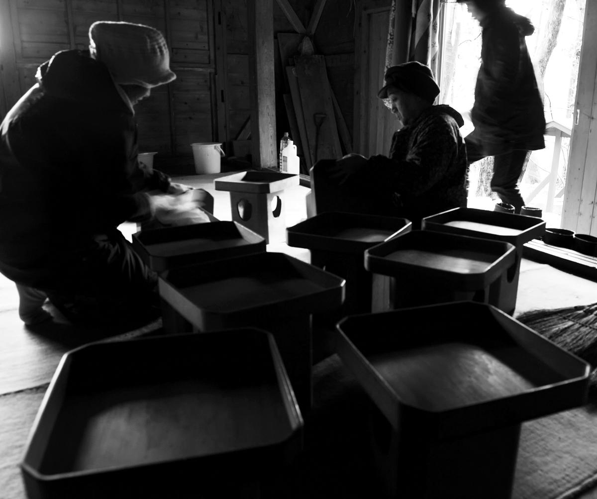 写真下、社殿内で神具の準備と清掃をする女衆。白神山地の麓にある集落の師走は寒い