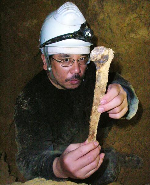 焦げた上腕骨を手にする筆者②。最初に発掘された
