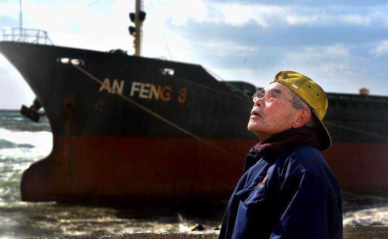 座礁した貨物船の横で空を見上げながら天候を心配する伊勢親方