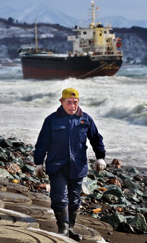 座礁船を背に海岸線を歩く親方。事故当時は、重油の刺激臭が充満し、マスクをしないで歩くのが苦痛だったという