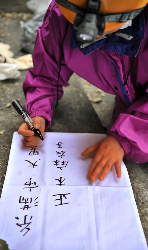 納骨袋に収骨者の氏名を書き込む麻衣子さん、糸満市で