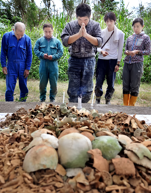 発掘した遺骨を前に祈りを捧げる楠田誠一郎・実行委員長(中央)ら