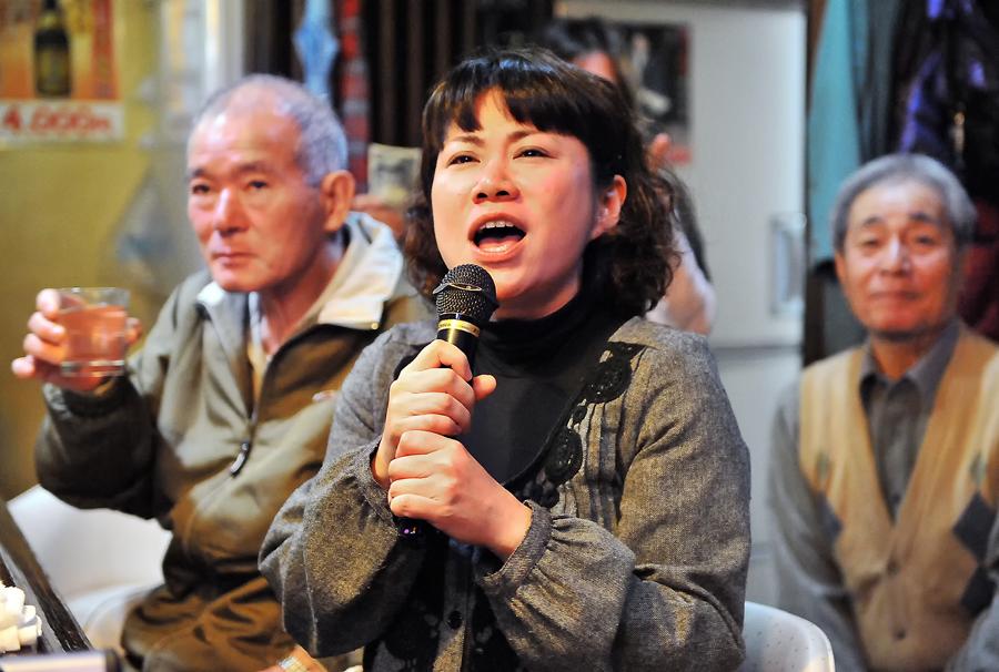 泡盛で上機嫌になった国吉さん(左)の前で大好きな曲を披露する、那覇市で