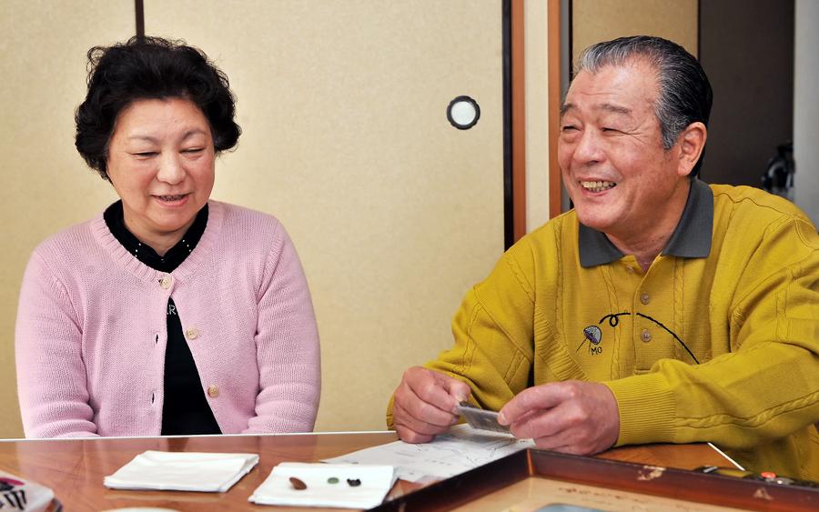 豊次さんの認識票を手に笑顔を見せる善夫さんと良江さん