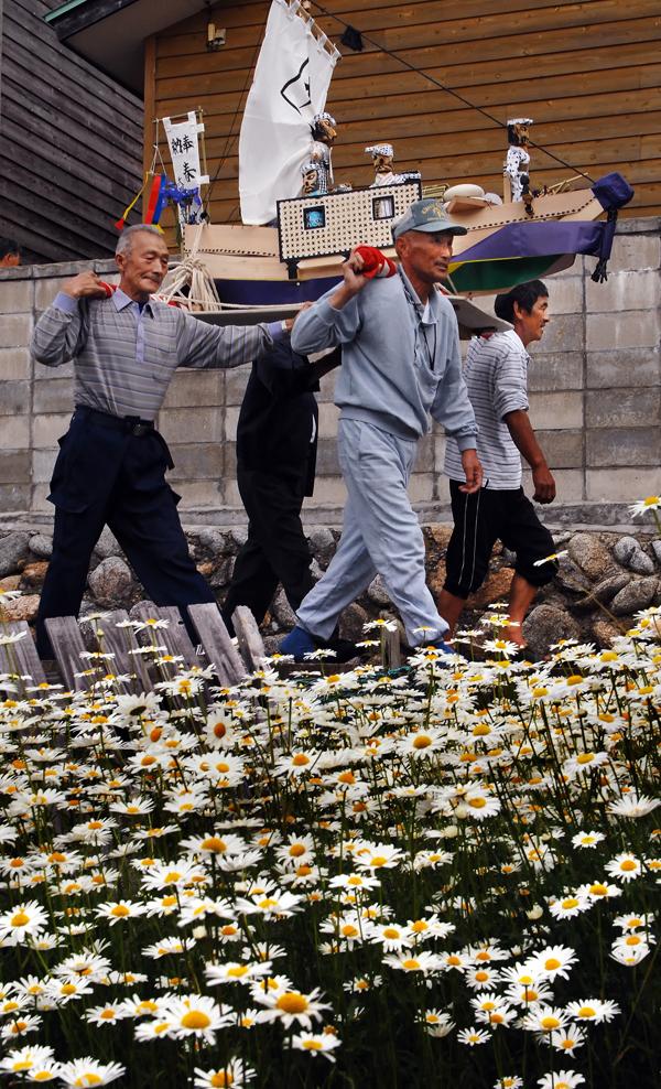 キク科の花が咲く民家の庭先を歩く春日丸の一行