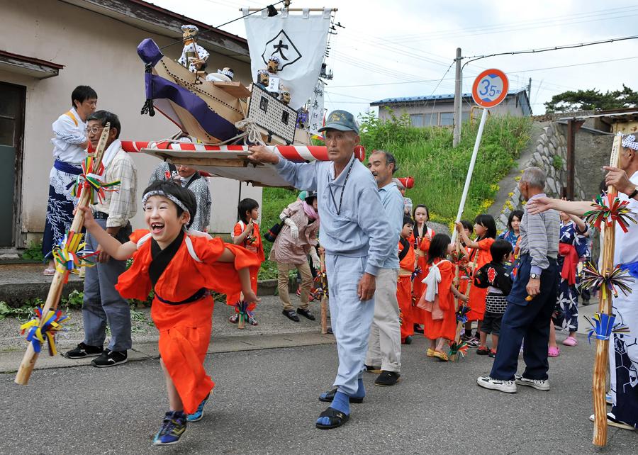 男衆が担ぐ神輿の下を弾ける笑顔で男の子が走り抜けます