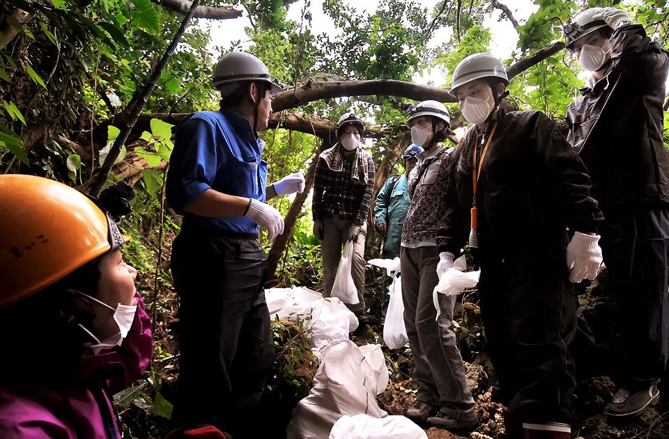 楠田委員長から(左から2人目)、収集に当たっての注意事項を聞くメンバー、糸満市で