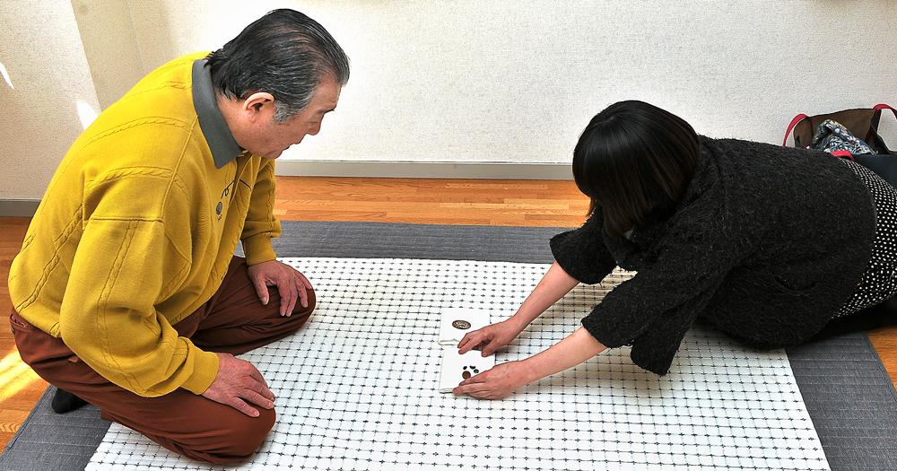 善夫さん(左)に認識票などを手渡す麻衣子さん、東京都で