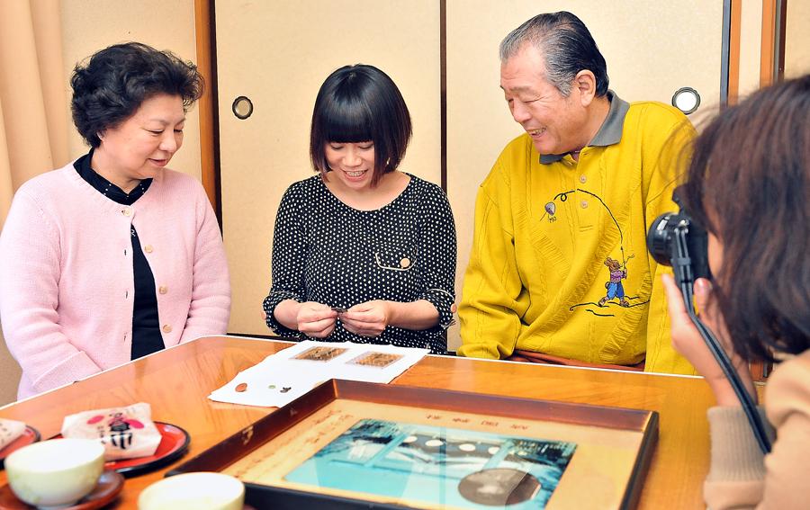 善夫さんご夫妻のもとへ届けた認識票に、「帰って来れて良かったね」と、話しかける麻衣子さん(中央)。右手前で取材するのは朝日新聞の伊藤恵里奈記者