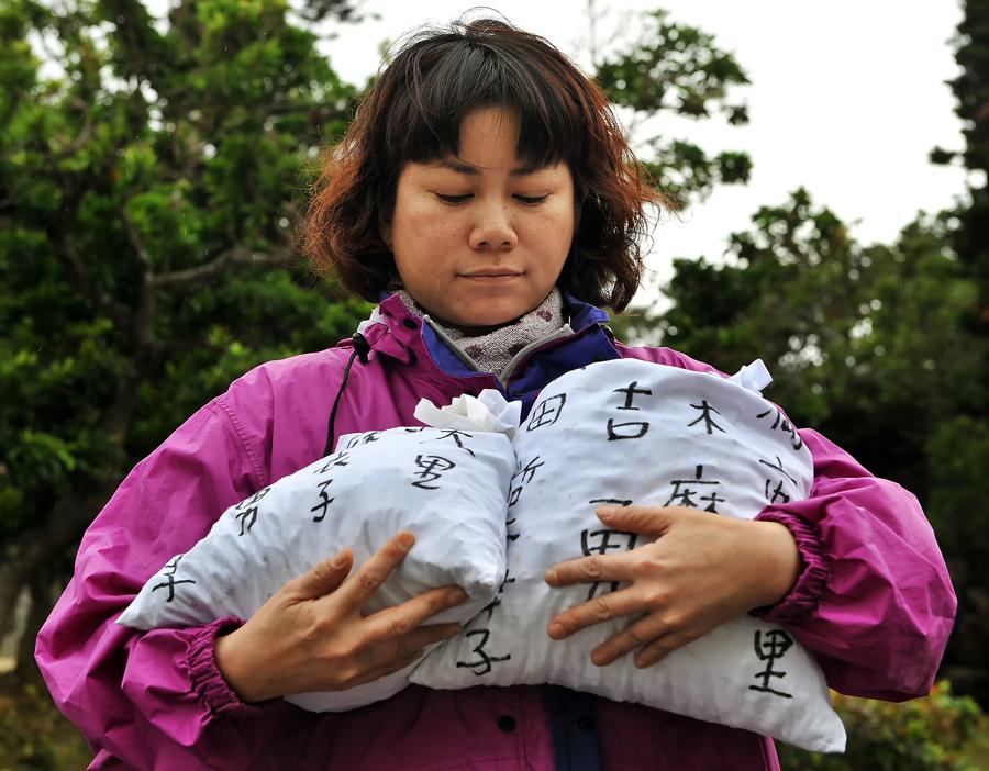 写真上、納骨袋に入れた遺骨を愛おしむように抱きかかえる麻衣子さん、糸満市の平和祈念公園で