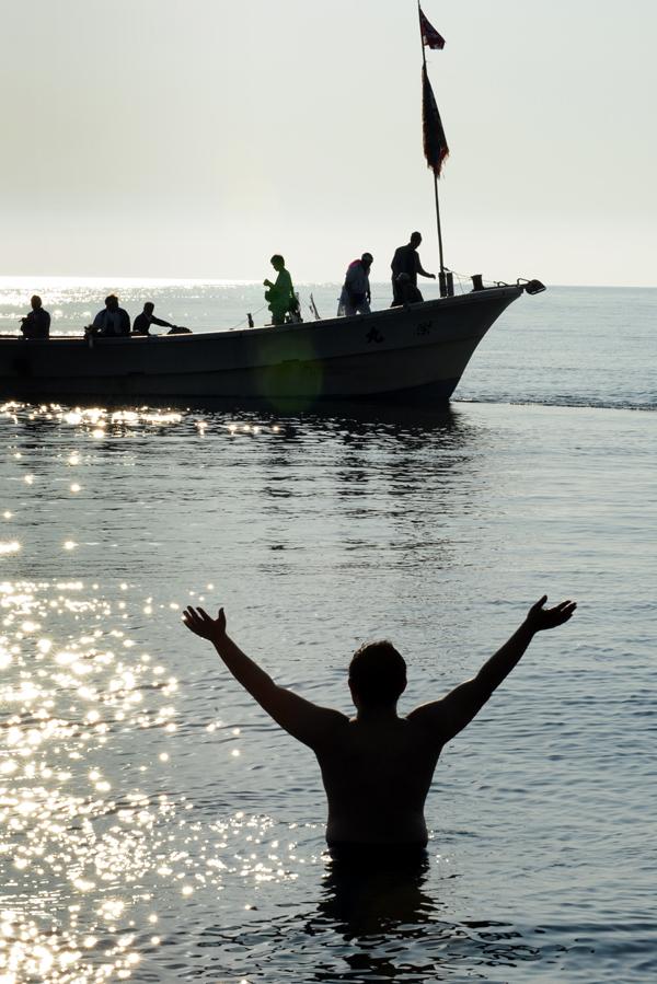春日丸が積み込まれた漁船に手を振る若衆
