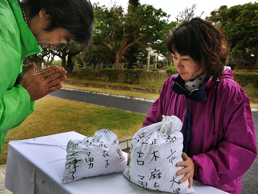 写真下、認識票が出た壕の遺骨を納骨する麻衣子さん。遺骨収集情報センターの職員が手を合わせて迎えた、糸満市の平和祈念公園で
