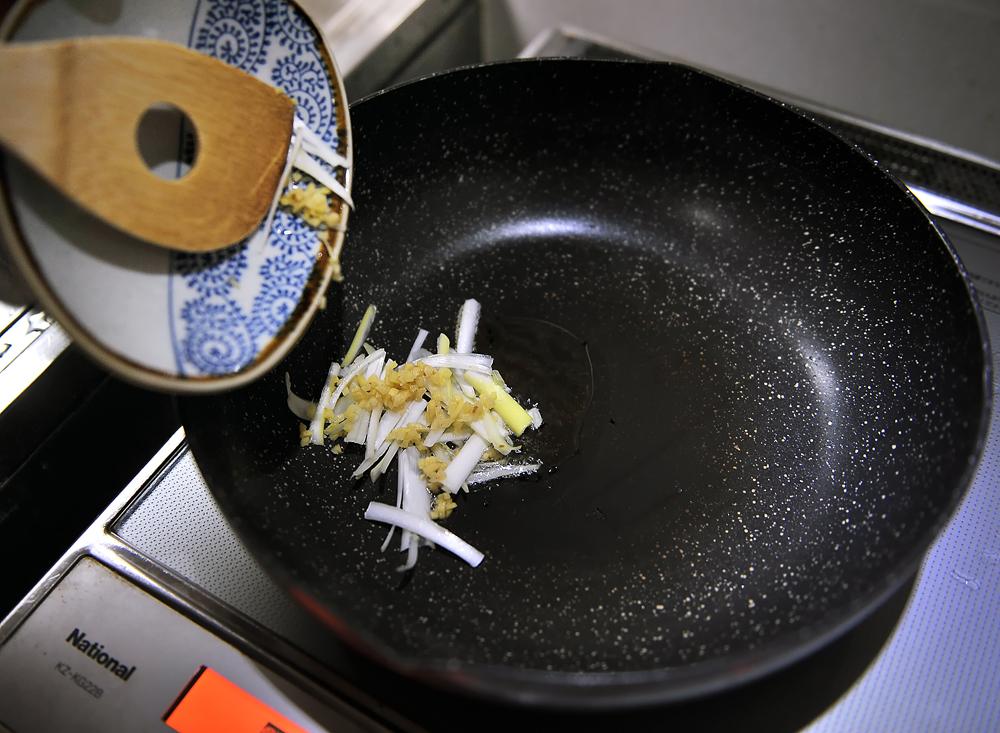 刻んだ白ネギとニンニクをゴマとサラダのミックス油で炒める