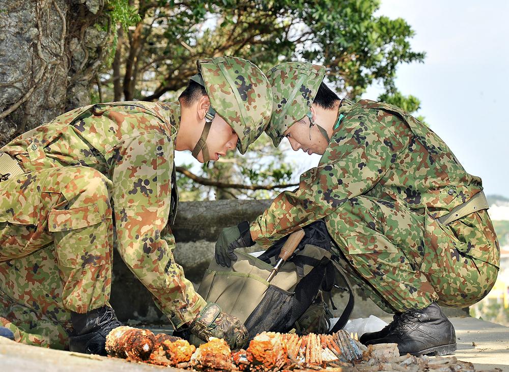 糸満市大里の陣地壕などから出た不発弾の処理に来た若い自衛官ら。松木さんはどんな思いで彼らの活動を見つめているか