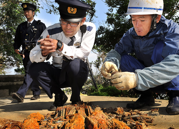 若い警察官と一緒に不発弾を見る国吉さん(右端)