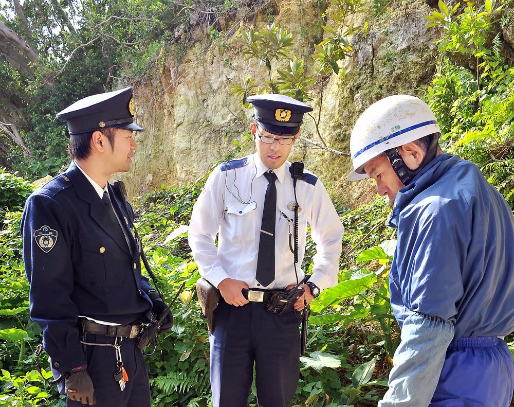 糸満市大里の陣地壕付近から掘り出した不発弾処理のため、警察官と相談する国吉勇さん(右端)
