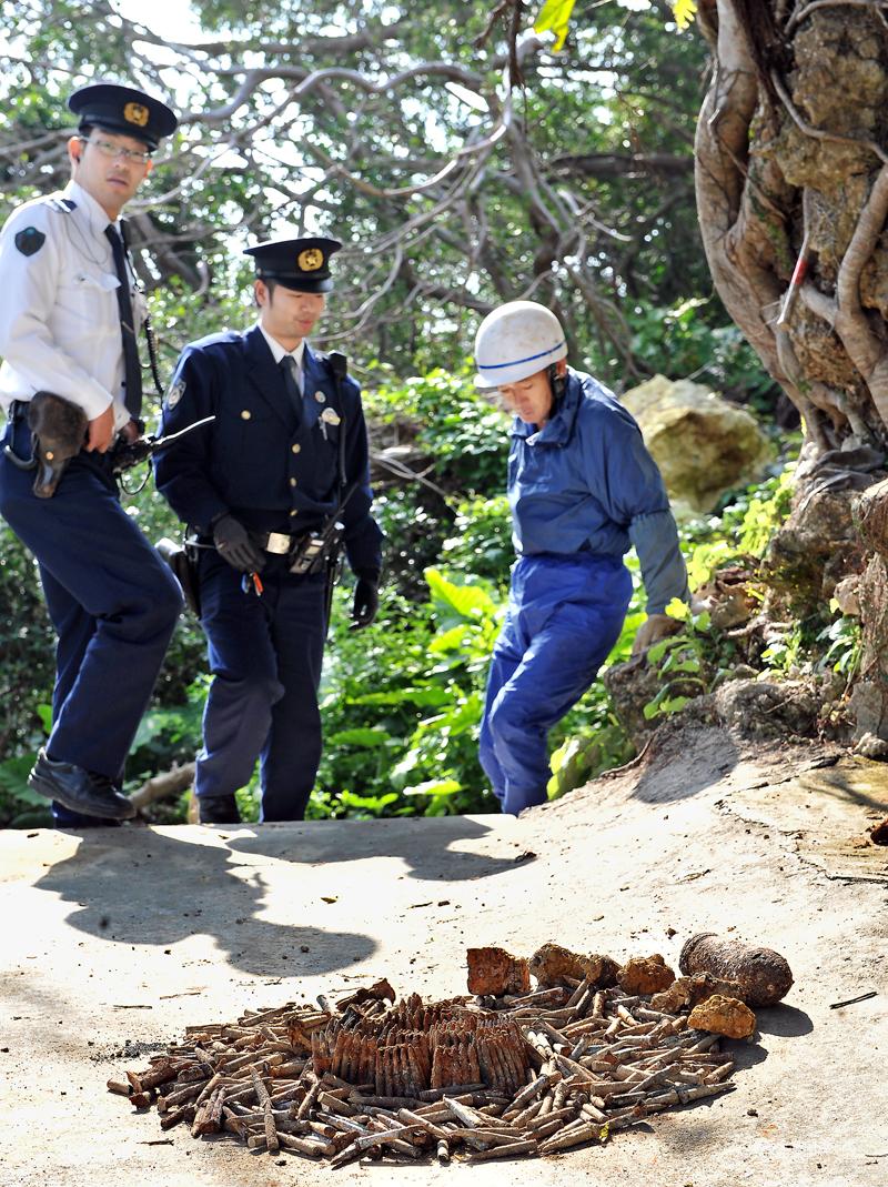 大里の陣地壕などから出た不発弾を警察官らに説明する国吉さん