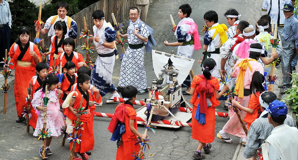 稲荷神社の前で、舟の周りを踊りながら回る神事の列