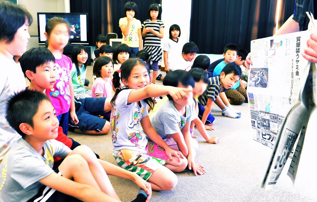 白神山地で子育てするシノリガモの記事が掲載された朝日新聞を見る子どもたち=深浦町で(個人情報保護のため画像の一部を加工)