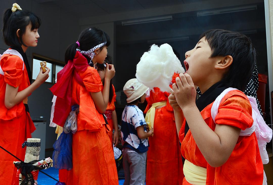 手作りの綿菓子にかぶりつく坊や。子供は地域の宝物だ