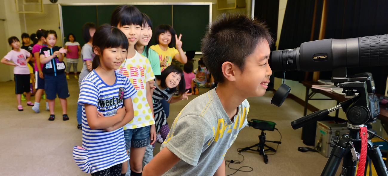 撮影と観察をするために使うフィールドスコープをのぞく子どもたち