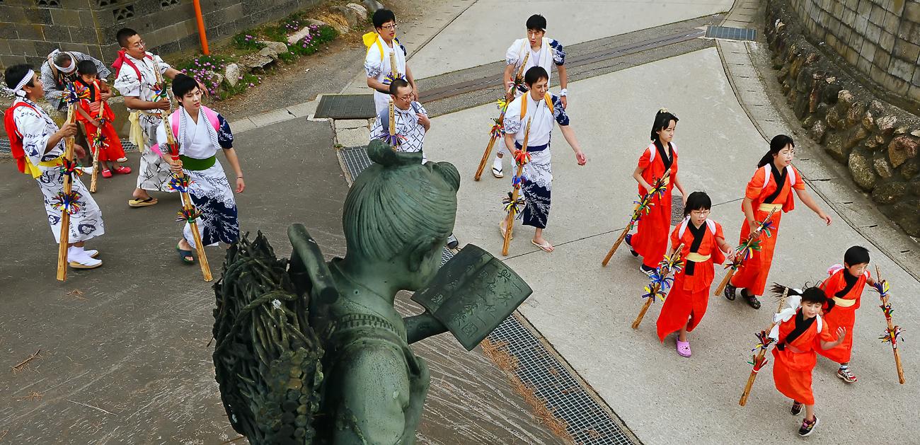 小学校跡が公民館に建て替えられた。その名残りの二宮金次郎像に見守られながら進む神事の列