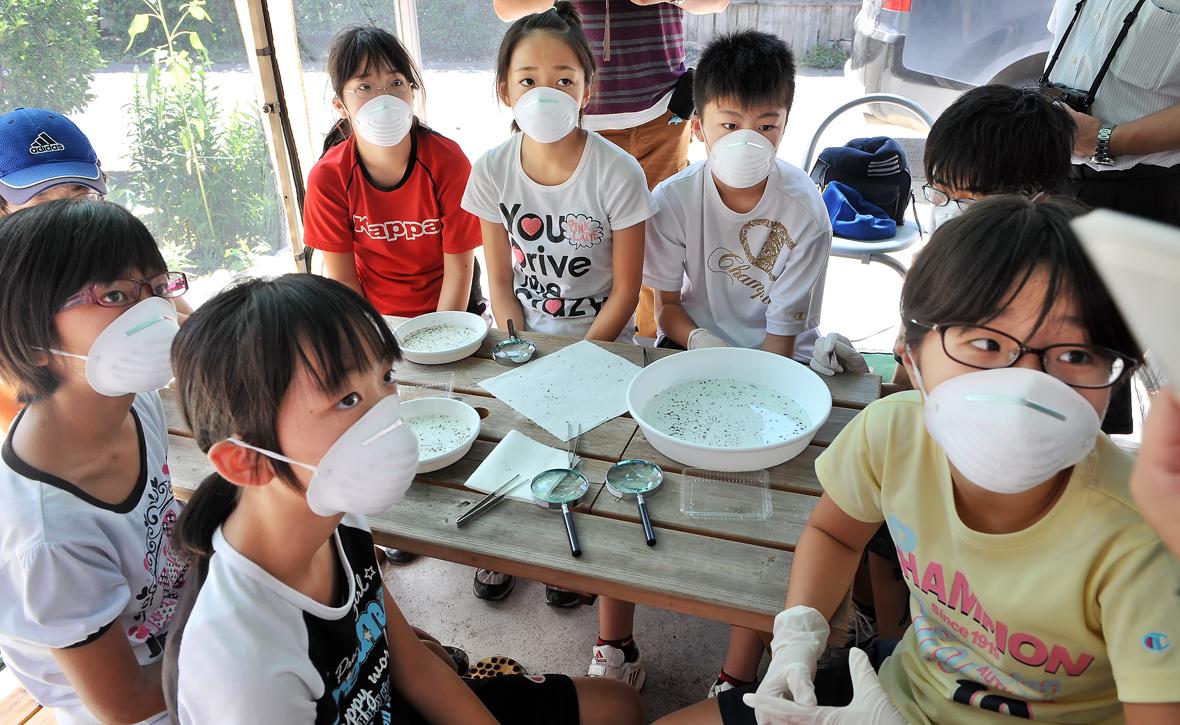 シノリガモのフンを分析し、その食性を調査する手法を聞く6年生の児童ら