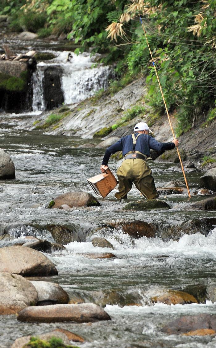 川の中に立ち入って魚を獲る釣り師