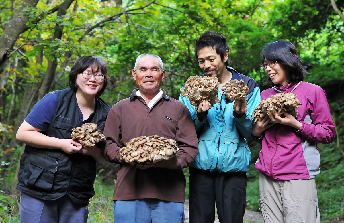 収穫したマイタケの一部を手に持ってキノコ狩りメンバーで記念撮影