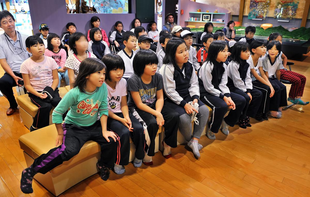 エコミュージアムでビデオを視聴する児童たち