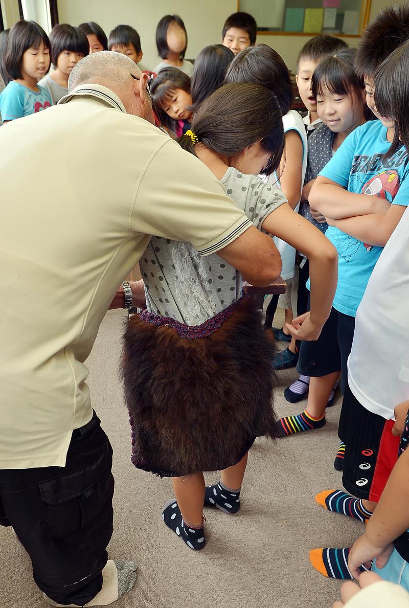 猟仲間のお孫さんに、クマの腰当てを着けてあげる親方