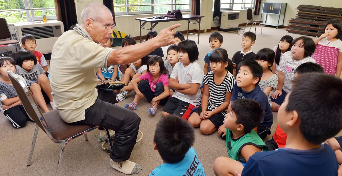 3年生の児童たちにマタギの心得を語る伊勢親方=町立深浦小学校で